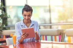 Härlig kvinna för blandat lopp med en afro frisyr som rymmer en digital minnestavla på coffee shop royaltyfri bild
