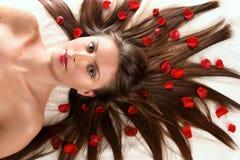 härlig kvinna för blommapetalsred Arkivfoto