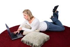 härlig kvinna för datorgolvbärbar dator Arkivbild