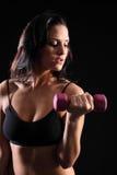 härlig kvinna för idrottshall för bicepkrullningsövning Arkivfoto