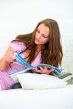 härlig kvinna för soffatidskriftavläsning Royaltyfri Fotografi