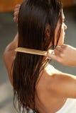 Härlig kvinna Hairbrushing hennes långa våta hår Den unga asiatiska flickan som kammar hår med, fingrar isolerat på vitbakgrund Fotografering för Bildbyråer