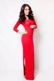 Härlig kvinna i anseende för lockigt hår för lång röd klänning sunt arkivbilder