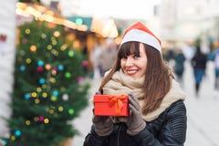 Härlig kvinna i ask för gåva för santa hattinnehav på julmor Arkivbilder