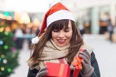 Härlig kvinna i ask för gåva för santa hattinnehav på julmor Royaltyfri Foto