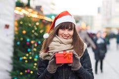 Härlig kvinna i ask för gåva för santa hattinnehav på julmor Royaltyfria Bilder