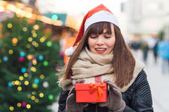 Härlig kvinna i ask för gåva för santa hattinnehav på julmor Royaltyfri Bild