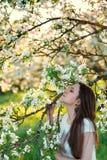 Härlig kvinna, i att blomstra äppleträd Arkivfoto
