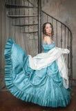 Härlig kvinna, i att fladdra den medeltida klänningen på trappan Royaltyfria Foton