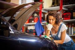 Härlig kvinna i auto mekaniker för overaller med en skiftnyckel Royaltyfri Fotografi