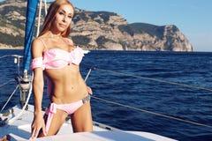 Härlig kvinna i baddräkt som kopplar av på yachten i det öppna havet Royaltyfri Fotografi