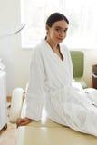 Härlig kvinna i badrock i Cosmetologyrum på den Spa salongen Royaltyfri Foto
