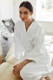 Härlig kvinna i badrock i Cosmetologyrum på den Spa salongen Arkivbilder