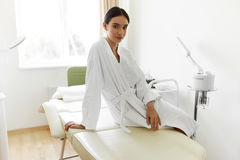 Härlig kvinna i badrock i Cosmetologyrum på den Spa salongen Arkivfoton