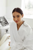 Härlig kvinna i badrock i Cosmetologyrum på den Spa salongen Fotografering för Bildbyråer