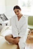 Härlig kvinna i badrock i Cosmetologyrum på den Spa salongen Royaltyfri Bild
