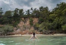 Härlig kvinna i bikini som går i havet på den tropiska stranden arkivbild