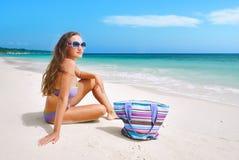 Härlig kvinna i bikini som solbadar på sjösidan Royaltyfri Bild