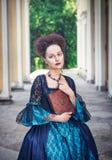 Härlig kvinna i blå medeltida klänning med boken Arkivbilder