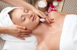 Härlig kvinna i brunnsort och att ha en ansikts- massage arkivfoto