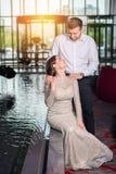 Härlig kvinna i chic klänningblickar in i ögonen av mannen i den vita skjortan arkivbilder