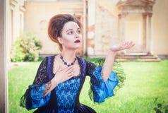 Härlig kvinna i den blåa medeltida klänningen som sträcker handen till someth Arkivfoton