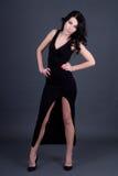 Härlig kvinna i den långa svarta klänningen som poserar över grå färger Royaltyfri Foto