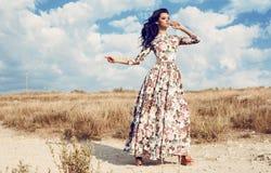 Härlig kvinna i den lyxiga blom- klänningen som poserar i sommarfält Royaltyfri Bild