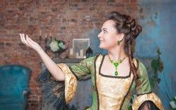 Härlig kvinna i den medeltida klänningen som sträcker handen till något Fotografering för Bildbyråer