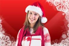 Härlig kvinna i den santa hatten rymma julgåvor Arkivfoton
