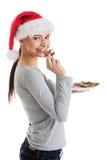 Härlig kvinna i den santa hatten som äter en kaka. Arkivbild