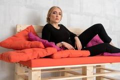 Härlig kvinna i den svarta dräkten som poserar på den låga soffan