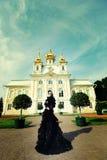 Härlig kvinna i den svarta klänningen som poserar bredvid slotten Royaltyfri Foto