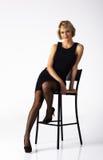 Härlig kvinna i den svarta klänningen som poserar sammanträde på en stol Fotografering för Bildbyråer