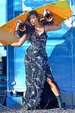 Härlig kvinna i den svarta vita klänningen, långt håranseende med wakeboad på bacgroundblåttjärnet, grafitti Arkivbilder
