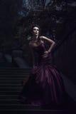Härlig kvinna i den violetta klänningen royaltyfria bilder