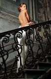 Härlig kvinna i den vita klänningen med naken baksida i slott. Arkivbilder
