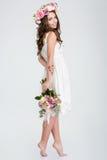 Härlig kvinna i den vita klänningen och roskransen som barfota står Fotografering för Bildbyråer