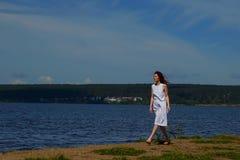 Härlig kvinna i den vita klänningen som går nära flodbanken royaltyfria bilder