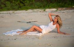 Härlig kvinna i den vita klänningen som ligger på stranden Royaltyfria Bilder