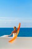 Härlig kvinna i den vita klänninghälsningen något från havet Arkivfoto