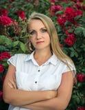 Härlig kvinna i den vita skjortan mot bakgrunden av en Bush av röda rosor Royaltyfri Bild
