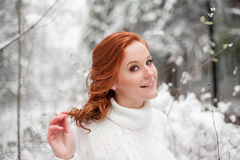 Härlig kvinna i den vita tröjan i snöig skog Royaltyfri Bild