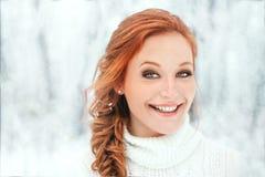 Härlig kvinna i den vita tröjan i snöig skog Royaltyfria Bilder