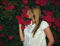 Härlig kvinna i det vita klänninganseendet nära en Bush med härliga ljusa röda rosor royaltyfria bilder
