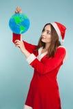 Härlig kvinna i dräkt för nytt år med ett jordklot Arkivbild