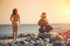 Härlig kvinna i en baddräkt som promenerar stranden mot bakgrunden av en pyramid av stenar Suddig kvinnlig med stenar på Royaltyfri Bild
