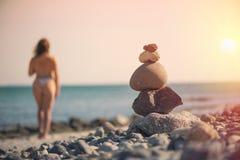 Härlig kvinna i en baddräkt som promenerar stranden mot bakgrunden av en pyramid av stenar Suddig kvinnlig med stenar på Royaltyfria Foton