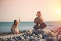 Härlig kvinna i en baddräkt som promenerar stranden mot bakgrunden av en pyramid av stenar Suddig kvinnlig med stenar på Royaltyfri Fotografi