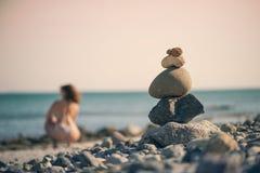 Härlig kvinna i en baddräkt som promenerar stranden mot bakgrunden av en pyramid av stenar Suddig kvinnlig med stenar på Arkivbild